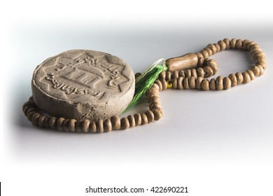 "Shia Islam prayer beads and clay from Karbala with the writing ""peace be upon you oh father of Abdullah"""