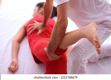 Shiatsu back and leg massage on female patient dressed in red.