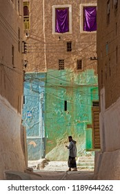 Shibam, Yemen - May 8, 2007: A young man in traditional clothes walks in the narrow streets. The Old City of Shibam is a UNESCO World Heritage City.
