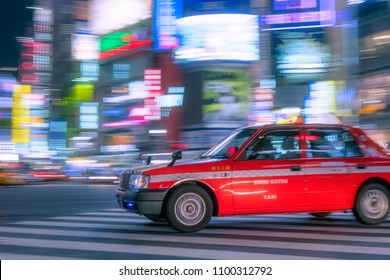Shibuya, Tokyo / Japan - April 30th 2017 : Japanese panning taxi traffic in motion blur by night with vivid and colourful lights and light-trails in the background.