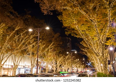 """SHIBUYA, TOKYO / JAPAN - DECEMBER 1 2018 : Scenery of Christmas illumination of """"Omotesando"""" street. Zelkova trees are colored with gold bulbs and the town glows brightly."""