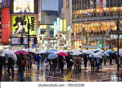 Shibuya, Tokyo, Japan - March 9, 2016 : crossing, crowd people on zebra crosswalk in Hachiko Square, Shibuya shopping street on rainy day, Shibuya is one of the world's most used pedestrian scrambles.