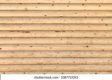 Shield with a large number of parallel wooden logs. Wooden wall from logs as a background texture / floor