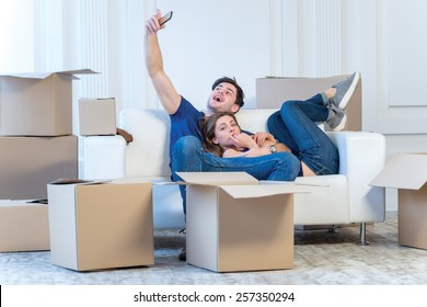 Shifting to a new life. A girl and a guy holding boxes for moving the hands and smiling at the phone camera while a couple in love making selfie at the window among boxes