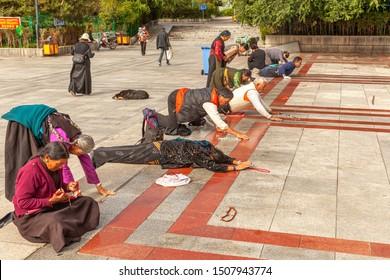 SHIGATSE, TIBET - AUGUST 13, 2019: Pilgrims prostrates in Tashilhunpo Monastery in Shigatse