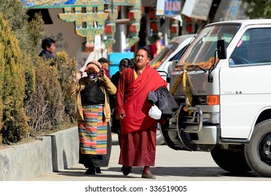 SHIGATSE, TIBET, CHINA-OCTOBER 24: Tibetan woman and monk walk around the lingkor or kora around Tashilhunpo-Heap of Glory monast.-seat of Panchen Lama on October 24, 2012. Shigatse-Tibet.