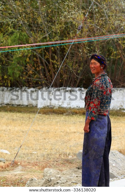 SHIGATSE, TIBET, CHINA-OCTOBER 24: Tibetan young mother calls her son playing at their homestead's yard to go back home on October 24, 2012-hamlet near Shigatse city-county and pref.-Tibet.