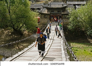 SHIGU, YUNNAN, CHINA, APRIL 26, 2009. People cross a stream on an old wood and chain bridge with a tile-roofed gate at the end on a sunny day in springtime.