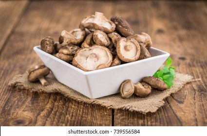 Shiitake mushrooms on an old wooden table as detailed close-up shot; selective focus
