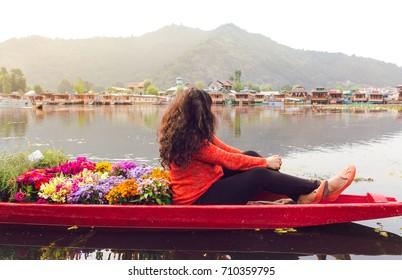 A Shikhara full of colorful flowers with a single travelling girl/woman. Backpacking girl on Dal lake, Srinagar, Kasmir, India. vibrant sunrise scene, beautiful, serene, peaceful, tranquil, wanderlust
