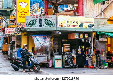 Shilin Night Market, Taipei, Taiwan, Republic of China - December 23, 2018 :  A scooter driver pauses