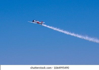Shiloh, IL—June 10, 2017 antique Japanese fighter warplane flies by trailing smoke