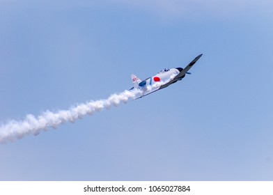 Shiloh, IL—June 10, 2017 antique Japanese navy fighter plane climbs and banks at airshow while trailing smoke
