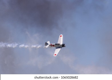 Shiloh, IL—June 10, 2017 antique Japanese navy fighter plane banks during airshow while trailing smoke