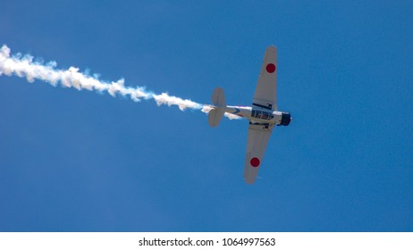 Shiloh, IL—June 10, 2017 antique white Japanese fighter plane flies past while banking to the right and trailing smoke
