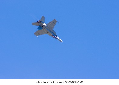 Shiloh, IL—June 10, 2017 navy fighter jet passes from left to right while rolling upside down at airshow
