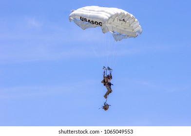 Shiloh, IL—June 10, 2017 paratrooper hangs from parachute risers while lowering pack prior to landing during airshow demonstration