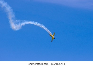 Shiloh, IL—June 10, 2017 pilot in yellow airplane conducts acrobatic maneuvers with trail of smoke showing path