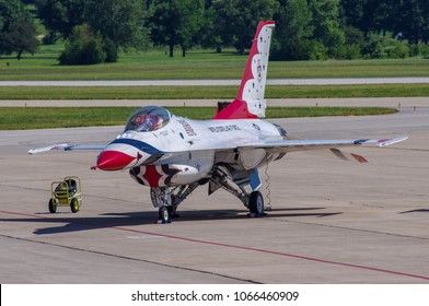 Shiloh, IL—June 10, 2017 red white and blue demonstration team jet fighter sits on tarmac next to fire extinguisher