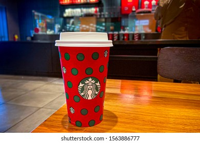 Shiloh, IL—Nov 17, 2019; Red and white 2019 Christmas print on Starbucks coffee cup rests on table at Scott AFB food court with counter and and customers in background
