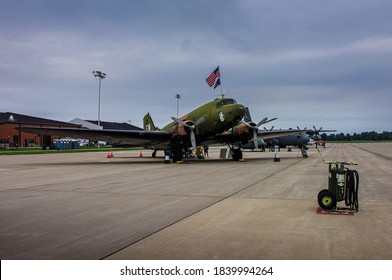Shiloh, IL--Sept 12, 2012; restored Vietnam era green brown and black AC-47 Spooky Gunship sits on tarmac in front of other aircraft with American flag flying from cockpit window