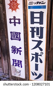 """SHIMANE, JAPAN - AUGUST 29, 2018: Old-style signs """"Chugoku Shimbun"""" (newspaper name, left) and Nikkan Sports (sporting goods corp, right) near Iwami Silver Mine; World Heritage Site"""