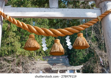 Shimenawa hang at the gate in front of the Japanese shrine at a springtime