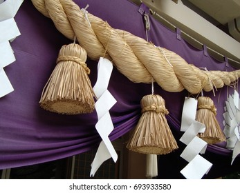 Shimenawa Rope; a thick, twisted straw rope with stripes of white paper hung around a place to ward off evil spirits.