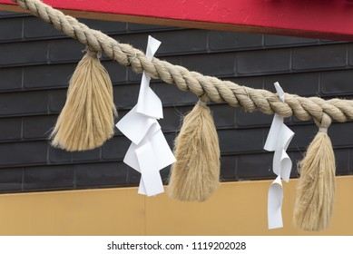 Shimenawa or shimekazari at Japanese shrine consists of a rice straw rope and white paper cut in strips