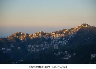 Shimla Himachal Pradesh India - February 04 2019 : Scenery of hosues line the hillside during sunrise in Shimla Himcahal Pradesh India