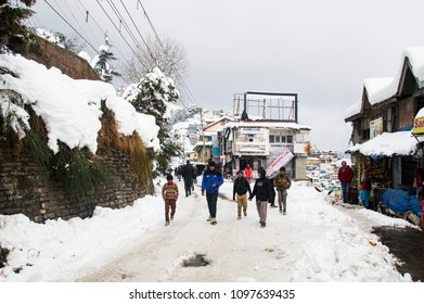 SHIMLA, INDIA - JANUARY 08, 2017: a group of friends walking on the snowy road in the city center