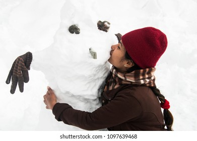 SHIMLA, INDIA - JANUARY 08, 2017: a girl kissing her snowman on a cheek in the thick snow