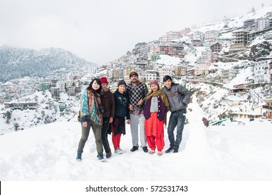 SHIMLA, INDIA - JANUARY 08, 2017:   an indian family taking a group picture with tourists at shimla during the heavy snowfall