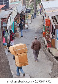 SHIMLA, INDIA - MARCH 19, 2014: Porter carrying a large load through one of the steep narrow streets of Simla. This means of transporting goods is common in Indian towns and cities