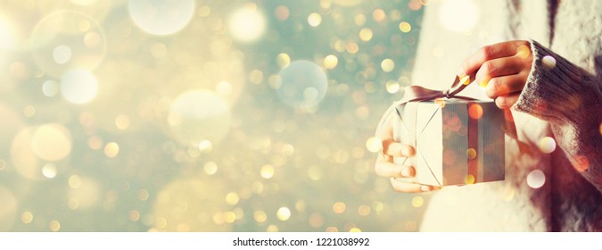 Shimmer background with snow, light bokeh. Woman hands opening gift box. Christmas, new year, birthday concept. Banner, copy space.