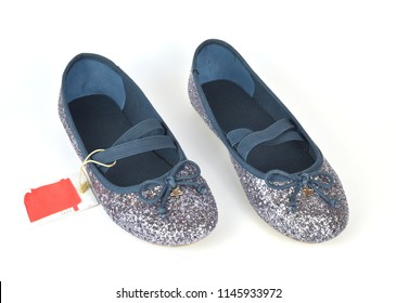 Shimmer silver blue ballerina flat shoes with crossed elastic drawstrings and a price tag on white background