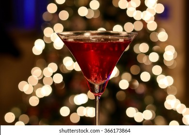 Shimmering holiday red martini cocktail against sparkling festive Christmas tree lights.