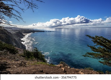 Shimmering reflective sunlight, blue skies, white clouds and waves splashing along the rugged Big Sur coastline, viewed from jagged cliffs of Ragged Point by Highway 1 on the California Central Coast.