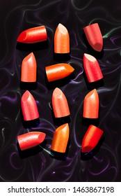 Shimmering sticks of lipstick marble  background