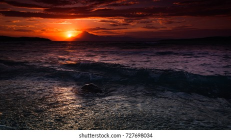 shimmering sunset seascape with waves reaching a beach with a rock