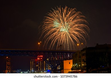 A shimmery gold and green firework bursts above the Flats district in downtown Clevleland Ohio