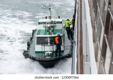 Shimonoseki, Japan - April 9 2015: A pilot disembarks to his pilot boat, from a small passenger ship, as it clears Shimonoseki Strait, the NW entrance to the Seto Inland Sea.