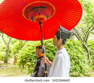 SHIMONOSEKI, JAPAN - MAY 19, 2019: A Japanese man in a white kimono holds a large red paper umbrella above a shinto priest in a rice planting festival parade.