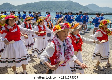 SHIMONOSEKI, JAPAN - MAY 3, 2018: Active senior citizens in colorful folk costumes perform a traditional folk dance on a boardwalk beside the ocean in Japan.