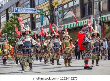 SHIMONOSEKI, JAPAN - MAY 3, 2018: Japanese men dressed as samurai warriors lead a colorful festival parade in Japan. The red banners read 'Taira no Tsunemori,' the name of a leader in the Heike clan.