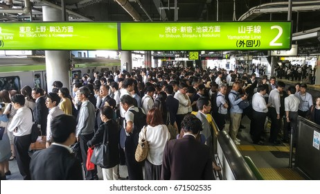 SHINAGAWA, TOKYO - June 10, 2016: Japanese commuters packed on the platform of Shinagawa Station waiting for train to Tokyo main commercial area, during morning rush hour.