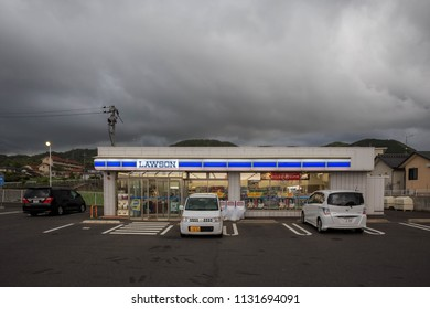 Shiname, Japan - May 30, 2018: Rural convenience store with large parking lot under dark storm clouds on the Shimane coast