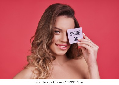Shine on!  Attractive young woman looking at camera and smiling while standing against pink background
