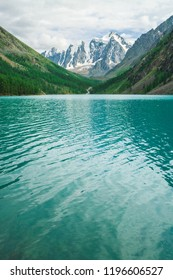 Shine water in mountain lake in highlands. Wonderful giant snowy mountains. Creek flows from glacier. White clear snow on ridge. Amazing atmospheric landscape of majestic Altai nature.