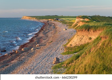 Shingle beach and cliff line of the Baltic Sea in sunset light near Heiligenhafen in Schleswig-Holstein, Germany
